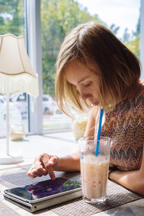 Young short-haired woman using tablet in cafe Photo