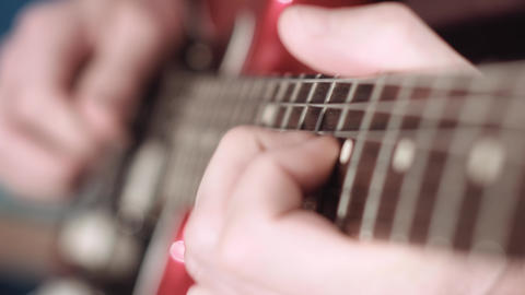 Electrig guitarist performing a solo, focus on fretting hand, cinematic Footage
