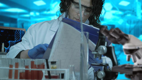 Woman researcher working in lab. Female researcher writing research report in Footage
