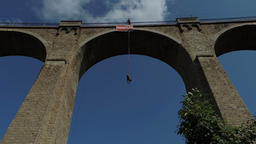 Rope jumping from high altitude of Bunovo bridge. Brave mature woman flying in Footage