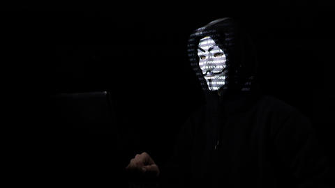 ROMANIA SEPTEMBER 2017 Anonymous masked hacker with hood committing cyber crime Live Action