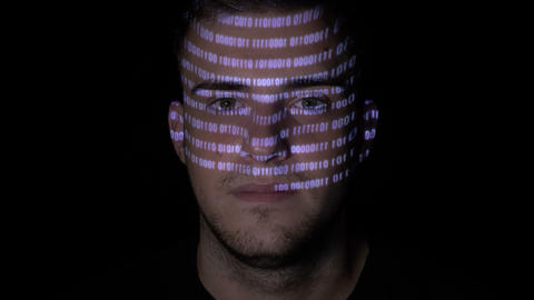 Running digital binary data code reflected on the face of a young man working on Footage