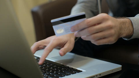 Man paying bill, shopping online, inserting credit card number. A man paying for Footage