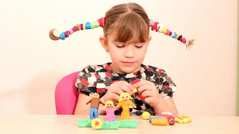 little girl make family figure with plasticine Footage