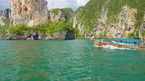 Boat with tourists floats along the rocky coast Footage