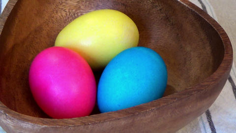 Zoom in Easter painted eggs in a wooden bowl Footage