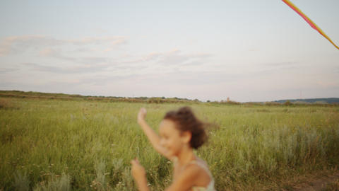 Girl with kite running on road Footage