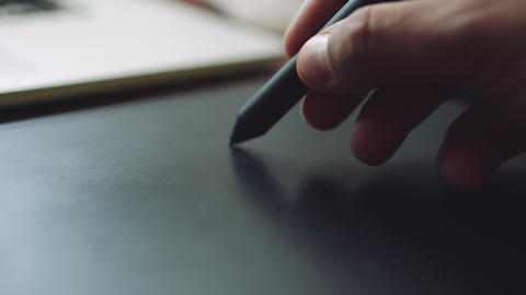 Designer working on a laptop with a graphics tablet Footage