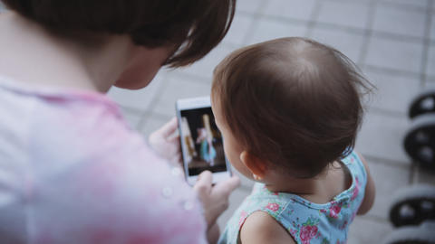 Woman showing something to her child on the smartphone Footage