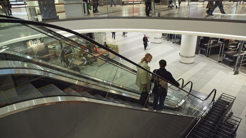 Two people down the escalator in the shopping centre Stockmann in St. Petersburg Footage