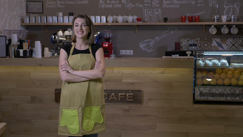 Female coffee shop owner standing in front of the counter being satisfied of her Footage