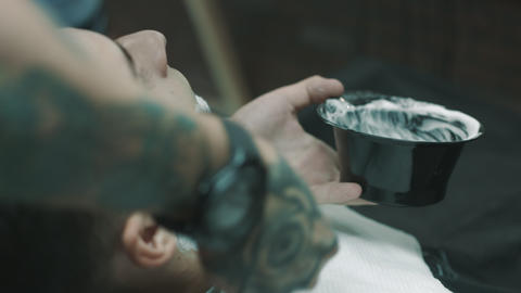 Barber putting some shaving cream on a client Footage