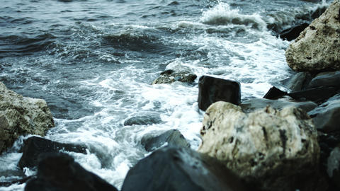 Waves beat against the rocks on the shore Footage