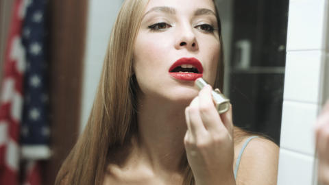 Beautiful blond woman paints her lips Footage