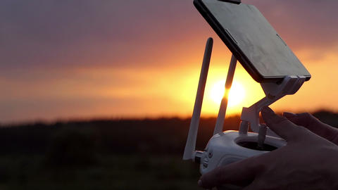 Woman's hands keep a control panel to operate a drone at sunset GIF