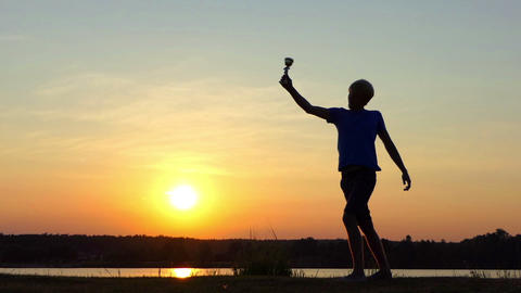 Sportive man raises his winner bowl happily at a lake in slo-mo Live Action