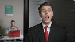 Young successful businessman in a suit bites, clicks his teeth in the office Footage