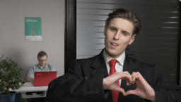 Young successful businessman in suit shows a sign of the heart, a sign of love Footage