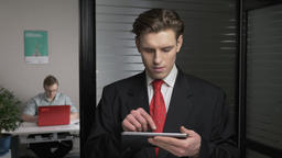 Young successful businessman in suit looks photo on tablet, using a tablet. Man Footage