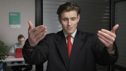 Young successful businessman in suit showing a come here sign. Man works on a Footage