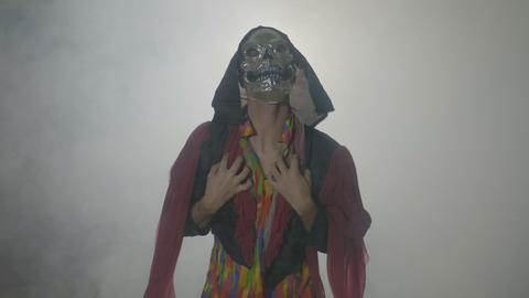 Possessed creature wearing a scary mask celebrating day of the dead on a foggy Footage