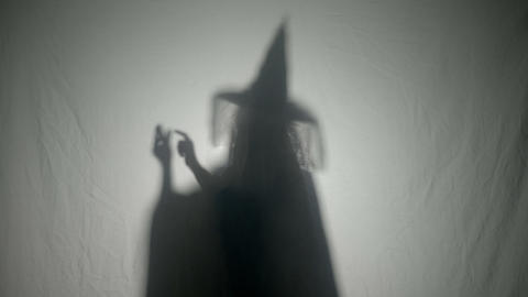Shadow silhouette of an evil witch dialing a phone number laughing and cursing Footage