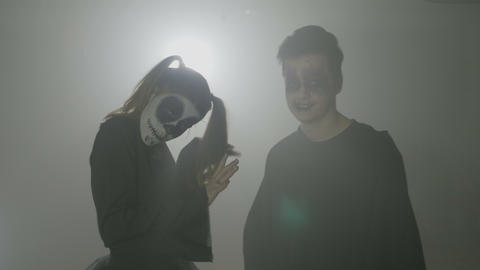 Young couple of college students dressed up as zombies on a background with fog Footage