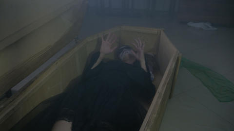 Coffin opening and female zombie with pigtails hair rises from it and evil Footage