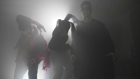 Halloween zombie squad walking from fog to village scaring the people in slow Footage