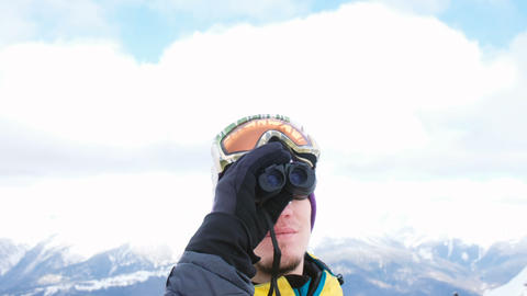 A man in ski goggles looking through binoculars at the mountains, enjoying the Footage
