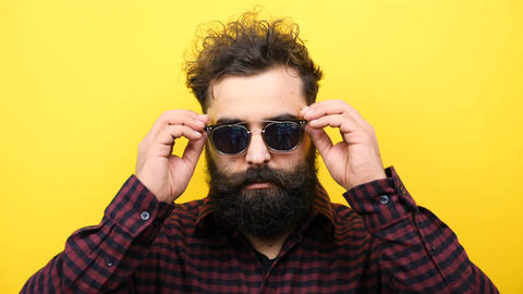 bearded hipster lowers his sunglasses on yellow background Footage