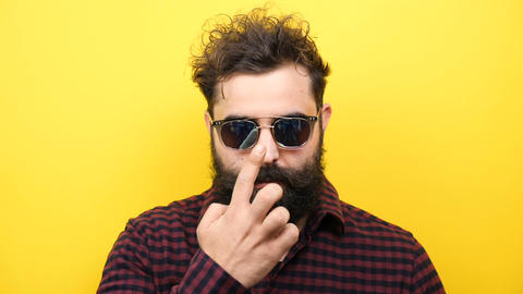 Hipster man on yellow background puts his sunglasses on Footage