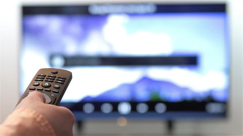 Hand changes the channels on smart TV remote control Footage