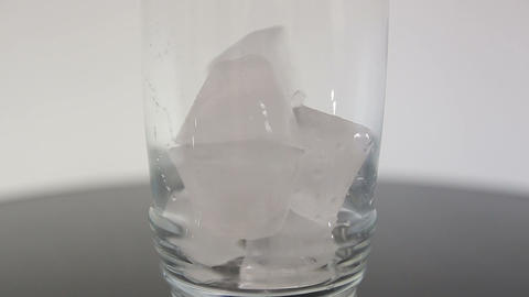 Falling ice cubes in a transparent glass isolated in white background Footage