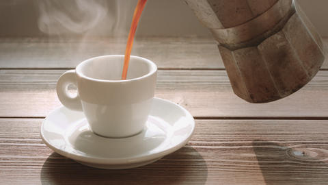 Person pours coffee in small cup Live Action