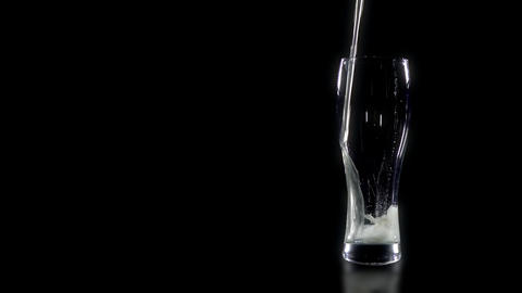 A glass of beer is poured on a black background Footage