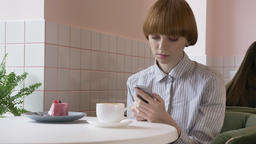 Young beautiful red-haired girl sitting in a cafe, using a smartphone, texting Footage