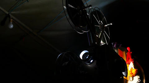 Vintage Retro Film cinema Projector Man is adjusting the film roll During Footage