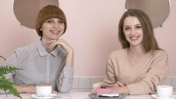 Two young caucasian girls sitting in a cafe and smiling, looking at the camera Footage