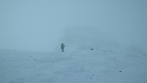 Hiker gets lost in the fog and snow of the mountain Footage