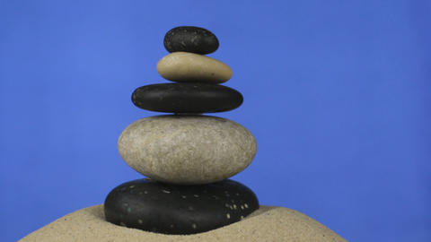 Rotation of the pyramid made of stones standing on the sand. Isolated Footage