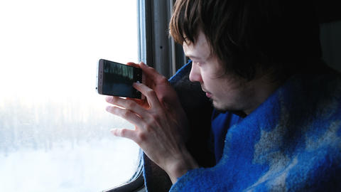 man in a rug travels by train and takes pictures of nature on the phone, the Footage