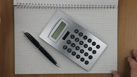 Calculator and pen in a notebook. Turn the notepad sheet to work Footage