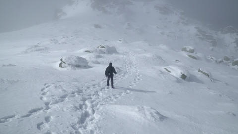 Tracking shot of hiker approaching the summit of the snowy mountain peak Footage
