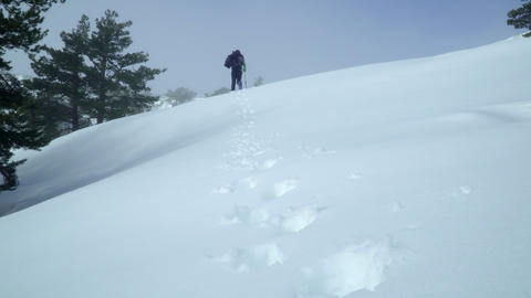 Woman walks away on the mountain leaving a trail of footsteps in the snow Footage