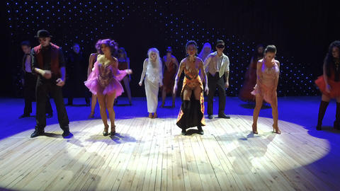 People in beautiful costumes and with greasepaint are dancing in modern theatre Footage