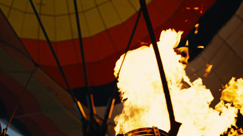 Low angle view of flaming burner and colorful hot air balloon envelope. Handheld Footage