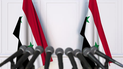 Syrian official press conference. Flags of Syria and microphones. Conceptual Footage