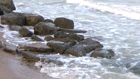 Waves breaking on big rocks at the sea shoreline on a windy day Footage