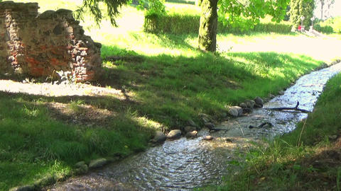Scenery with a glittery water stream, a stone bridge flowing in the summer creek Footage